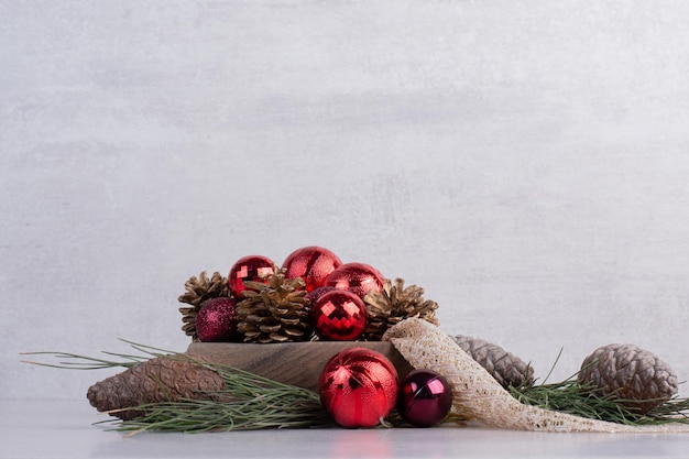 Kerstballen en dennenappel op witte tafel.