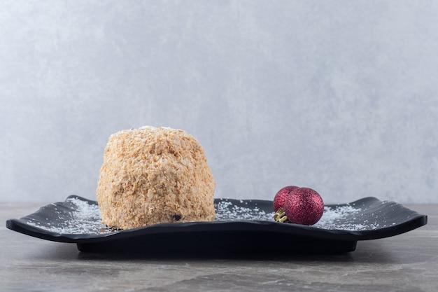 Kerstballen en een eekhoorncake op een zwarte schotel op marmeren oppervlak