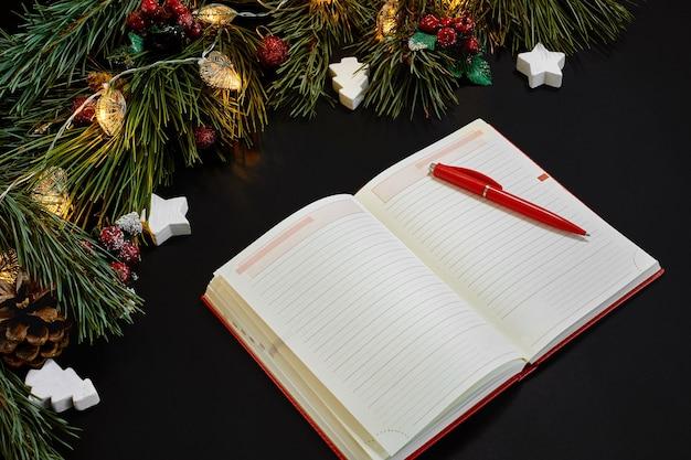 Kerstballen en notebook liggen in de buurt van groene sparren tak op zwarte achtergrond bovenaanzicht. ruimte kopiëren. stilleven. plat leggen. nieuwjaar