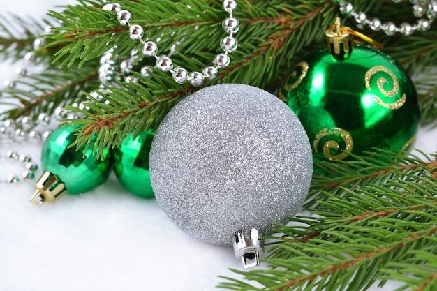 Kerstballen en slinger op een sparren tak