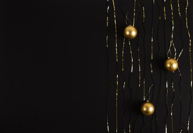 Kerstballen en slingers op een zwarte. nieuwjaar en kerstmis achtergronden met copyspace, plat lag.