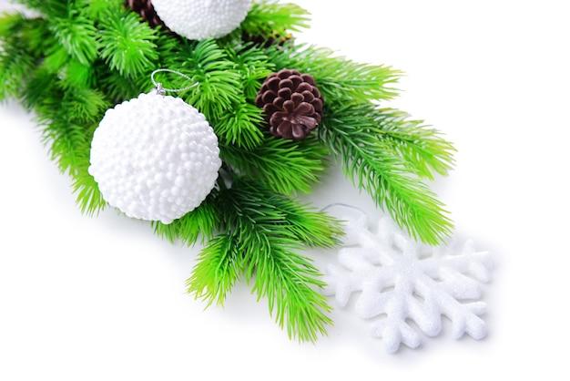Kerstballen en sneeuwvlok op dennenboom, geïsoleerd op wit