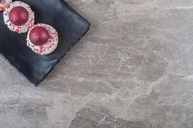 Kerstballen gestapeld op kleine donuts op een zwarte schaal op marmeren oppervlak
