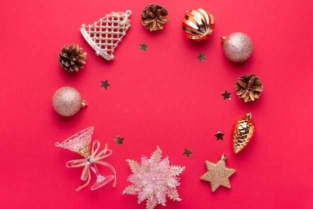 Kerstballen, gouden en roze decoraties rond frame, confetti op rode achtergrond met kopieerruimte. kerstkaart met ornamenten, bovenaanzicht