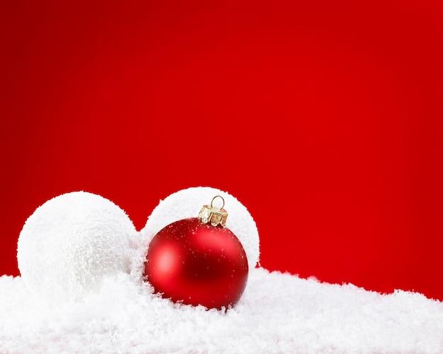 Kerstballen met sneeuw op rode achtergrond
