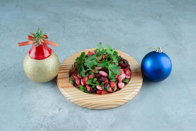 Kerstballen naast een schotel met peterselie gegarneerde vinegret salade op marmer.