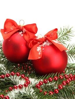 Kerstballen op dennenboom met sneeuw, geïsoleerd op wit