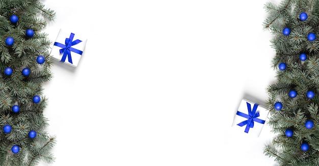 Kerstbanner met dennentakken, blauwe ballen en geschenken op een witte achtergrond.