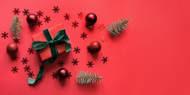 Kerstbanner met rode vakantiegift, kerstballen op rode ruimte