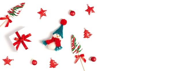 Kerstbanner met sneeuwpop, geschenken en kerstversiering op een witte achtergrond.