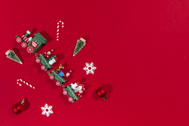 Kerstbanner trein speelgoed en nieuwjaar accessoires kerstboom, bal, snoepgoed, sneeuwvlok op rode achtergrond