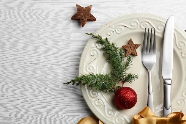 Kerstbestek op bord boven lichte houten tafel, close-up