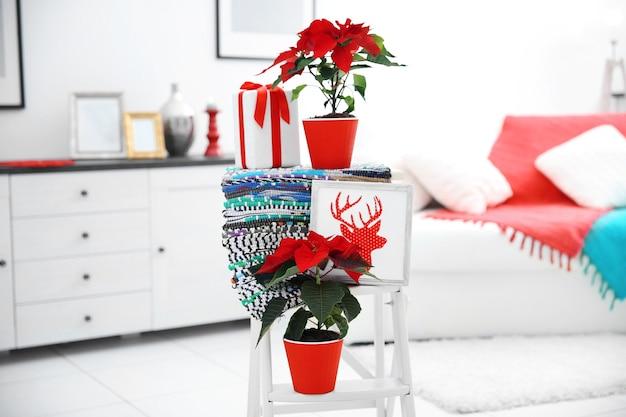 Kerstbloem poinsettia en decoraties op decoratieve ladder met kerstversieringen