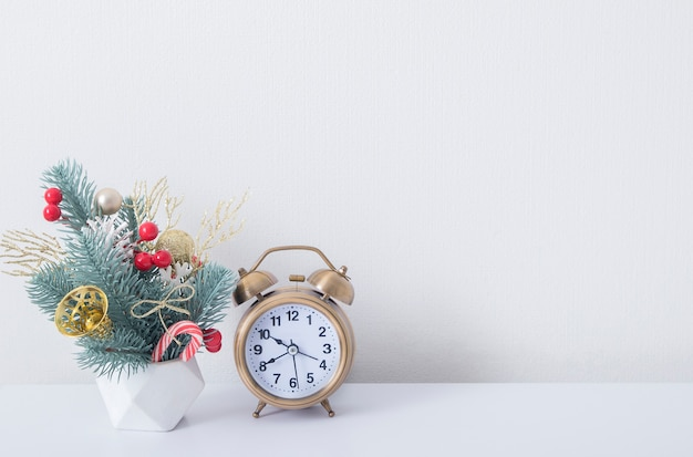 Kerstboeket met dennentakken en nieuwjaarsversieringen met wekker in wit interieur