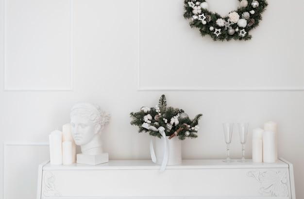 Kerstboeket van sparren en katoen in een wit interieur tegen de achtergrond van een witte piano