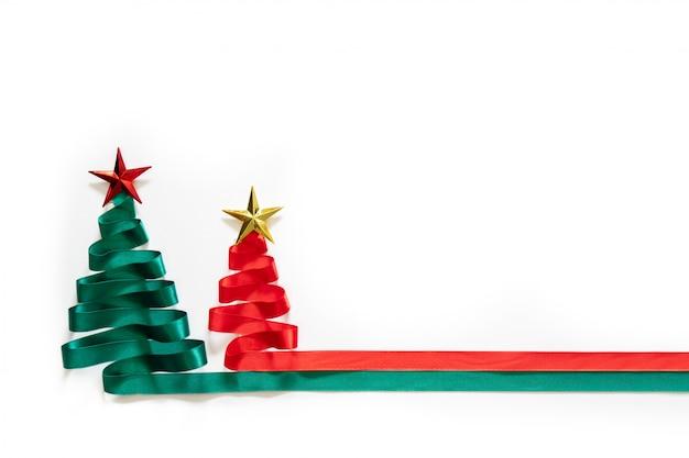 Kerstbomen gemaakt van groen en rood lint met gouden ster op witte achtergrond met coppy ruimte