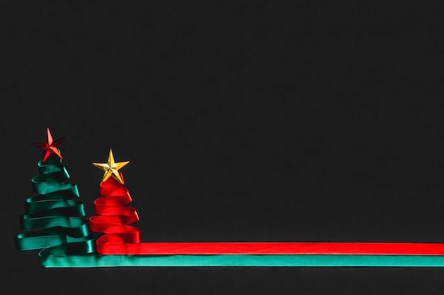 Kerstbomen gemaakt van groen en rood lint met gouden ster op zwarte achtergrond met coppy ruimte