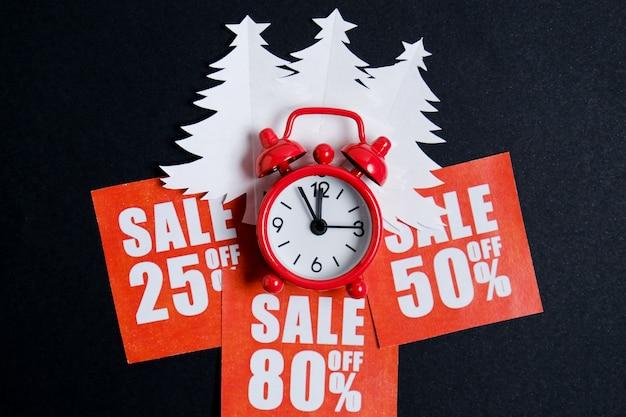 Kerstbomen gemaakt van wit papier op rode stickers met kortingen en een vintage klok