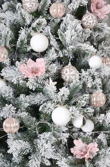 Kerstboom close-up versieren. decoratiebol, sneeuwgroene dennenboom, roze kerstspeelgoed en verlichting.