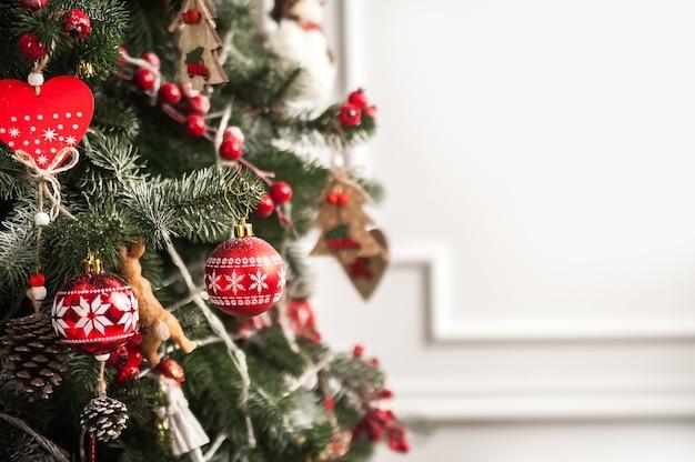 Kerstboom decor in rode stijl en bokeh kerstboom kerstversiering speelgoed close-up en kopieer ruimte hygge new years concept