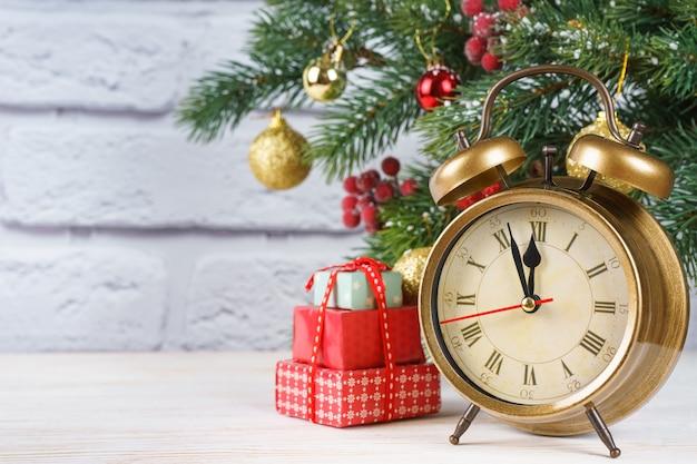 Kerstboom en aftellen naar het nieuwe jaar. bronzen retro klok, geschenkverpakkingen en ballen