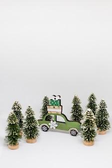 Kerstboom en blauwe auto met de winterachtergrond van de lichtensneeuw. kerst vakantie feest concept.