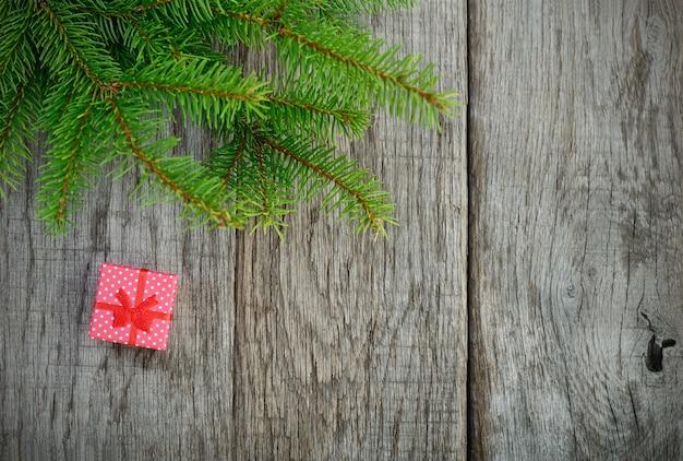 Kerstboom en cadeau op houten achtergrond