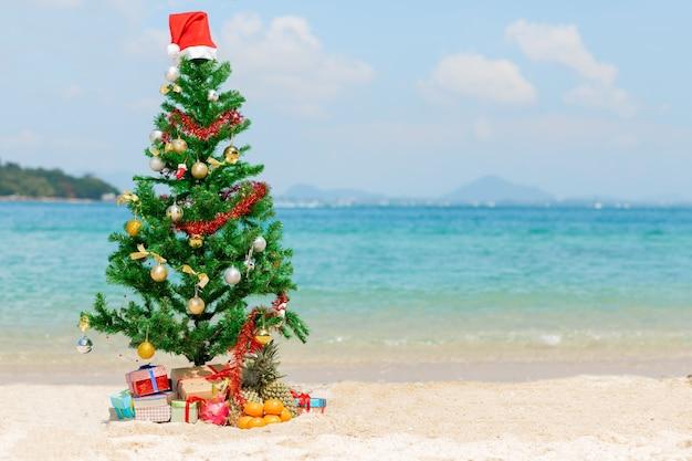Kerstboom en geschenken op strand achtergrond