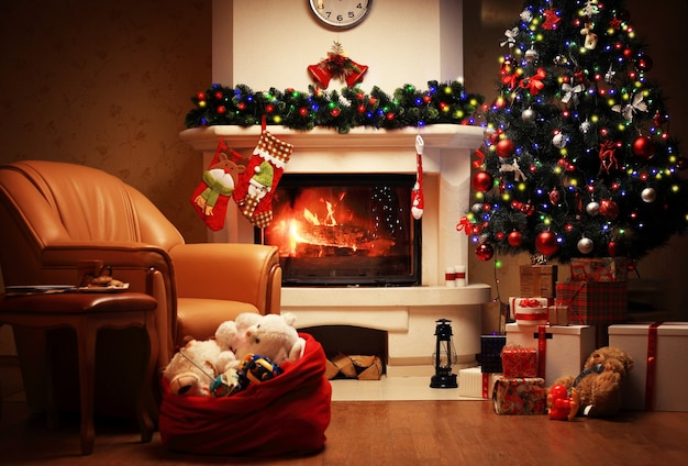 Kerstboom en kerst geschenkdozen in het interieur met een open haard