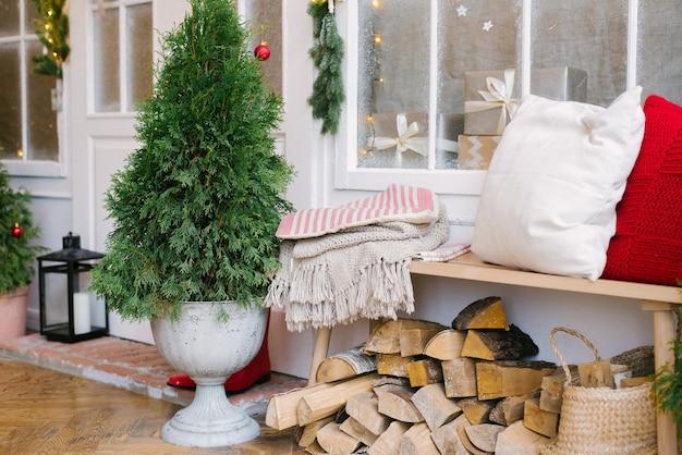 Kerstboom en kussens op een houten bankje