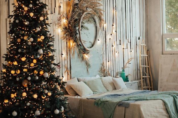 Kerstboom en slingers op de houten muur.