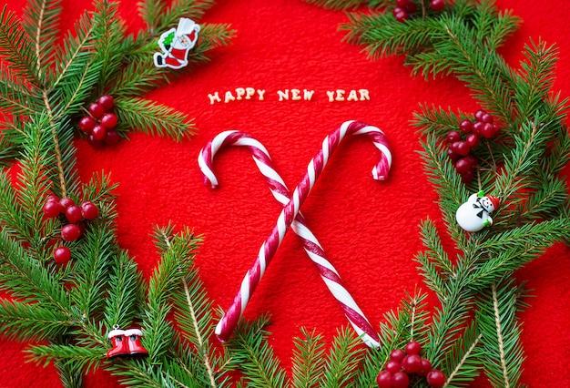 Kerstboom en snoep op een rode achtergrond met het briefkaart van het woorden gelukkige nieuwjaar