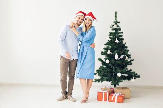 Kerstboom en vakantieconcept - gelukkige glimlachende familie die santahoeden draagt die thuis vieren.