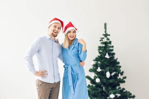 Kerstboom en vakantieconcept - gelukkige glimlachende familie die santahoeden dragen die thuis vieren.