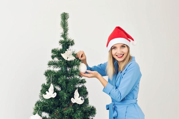 Kerstboom en vakantieconcept - gelukkige glimlachende vrouw die santahoeden draagt die thuis vieren.