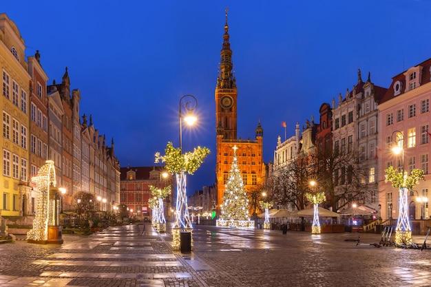 Kerstboom en verlichting op long market street en het stadhuis 's nachts in de oude binnenstad van gdansk