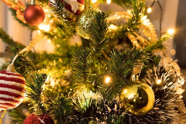 Kerstboom geassembleerd met ornamenten. rode, zilveren en gouden ballen, geschenkdozen, lichten, de kerstman en anderen. selectieve aandacht.