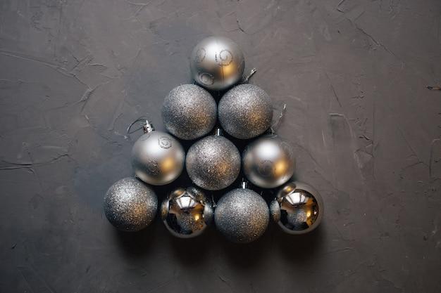 Kerstboom gemaakt door zilveren kerstballen op de donkere achtergrond met kopie ruimte