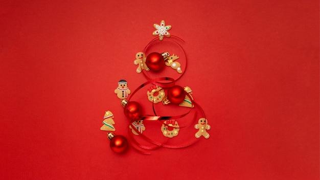 Kerstboom gemaakt met kerstkoekjes en kerstballen op rode tafel