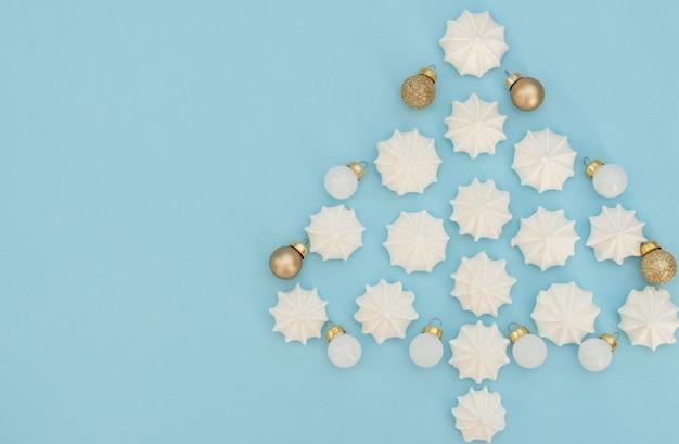 Kerstboom gemaakt met witte meringues met gouden en witte kerstversieringen