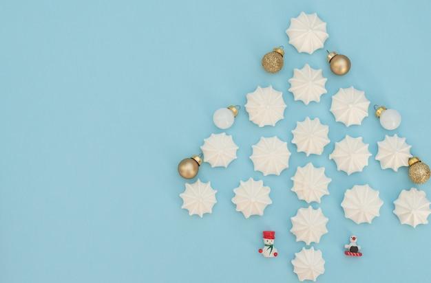 Kerstboom gemaakt met witte schuimgebakjes met gouden en witte kerstballen en houten kerstversiering op lichtblauwe achtergrond