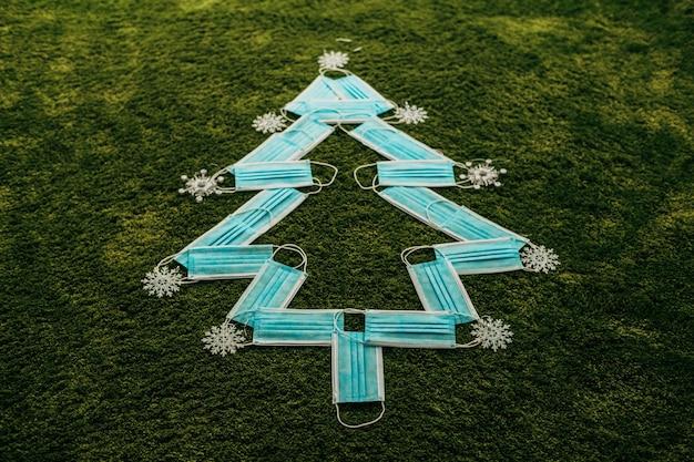 Kerstboom gemaakt van blauwe medische maskers op een groene achtergrond