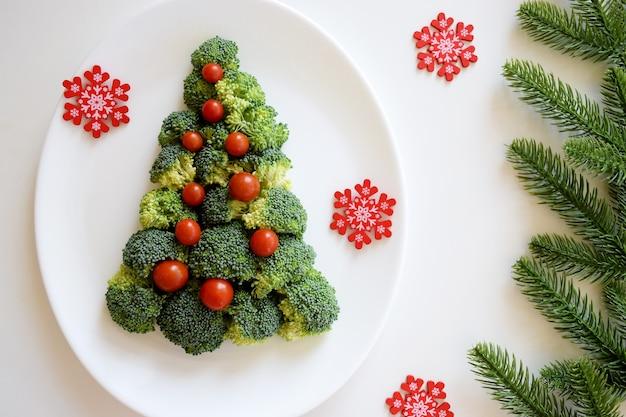 Kerstboom gemaakt van broccoli en kleine tomaten op witte plaat met rode sneeuwvlokken en fir tree takken op witte achtergrond.