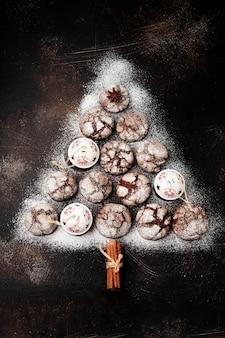 Kerstboom gemaakt van browniekoekjes met scheuren, kaneelkruiden, klokken en kerstmisspeelgoed op oud beton of stenen oppervlak. nieuwjaar concept