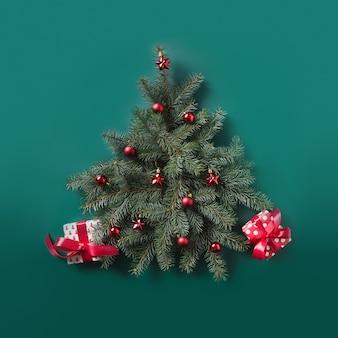 Kerstboom gemaakt van dennentakken en rode ballen met versierde rode geschenken