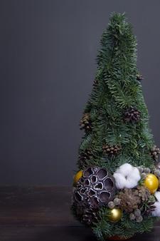 Kerstboom gemaakt van dennentakken en versierd met natuurlijke materialen en ballen