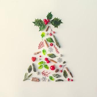 Kerstboom gemaakt van diverse winterplanten, bladeren, bessen en decoratie. winter vakantie concept. minimale nieuwjaar achtergrond.