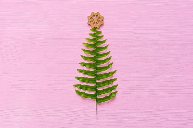 Kerstboom gemaakt van fern bladeren op een roze achtergrond. minimale kerst achtergrond. plat leggen. kopieer ruimte