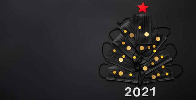 Kerstboom gemaakt van gezichtsmaskers en gouden feestelijke decorconfetti. 2021 oudejaarsavond kopieer ruimte.