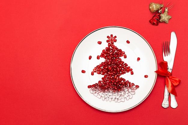 Kerstboom gemaakt van granaatappelpitjes op een wit bord